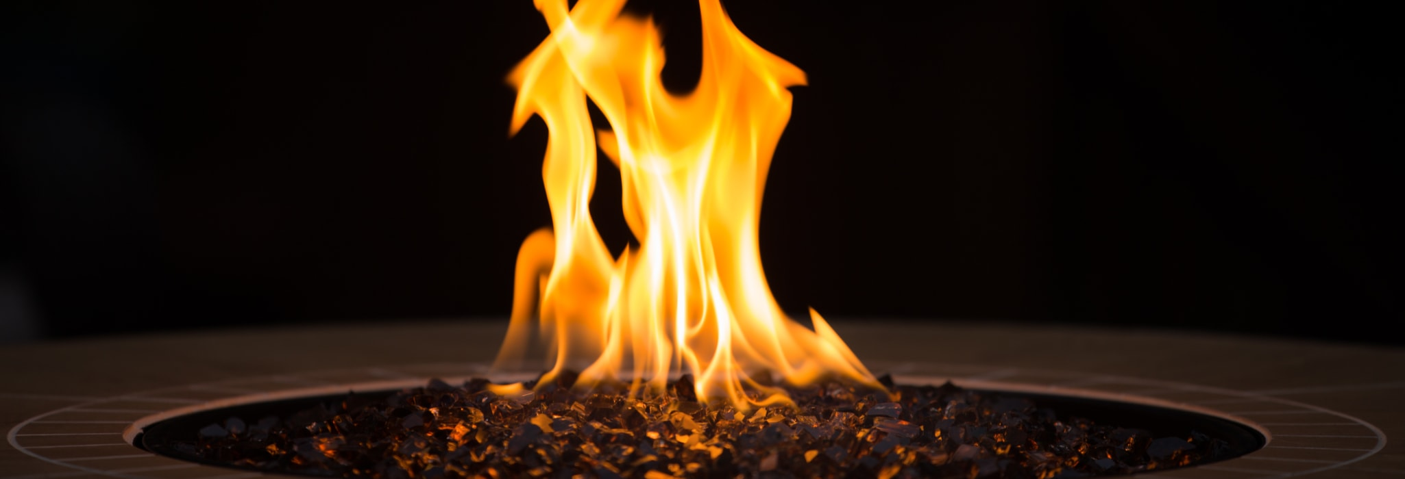 Close up of an outdoor fireplace with a big yellow flame and black background.